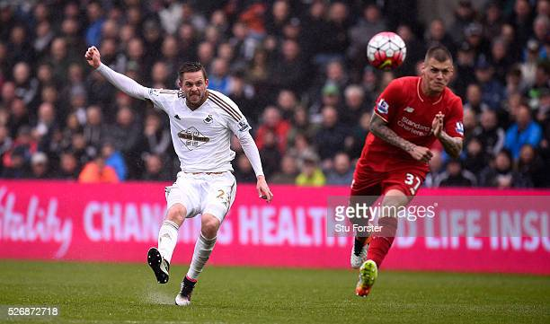 Swansea City player Gylfi Sigurdsson gets in a shot at goal despite the attentions of Martin Skrtel during the Barclays Premier League match between...