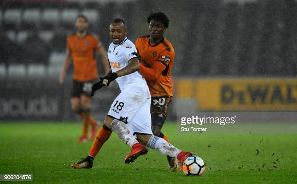 Swansea City player Jordan Ayew holds off Kortney Hause of Wolves during the Emirates FA Cup third round replay between Swansea City and...