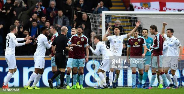 Swansea City players argue with referee Anthony Taylor after he awarded a penalty to Burnley during the Premier League match between Swansea City and...