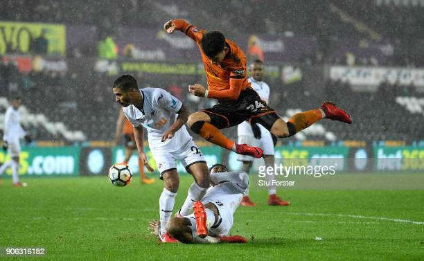 Swansea City players Leroy Fer and Kyle Naughton combine to thwart Wolves player Morgan GibbsWhite during the Emirates FA Cup third round replay...