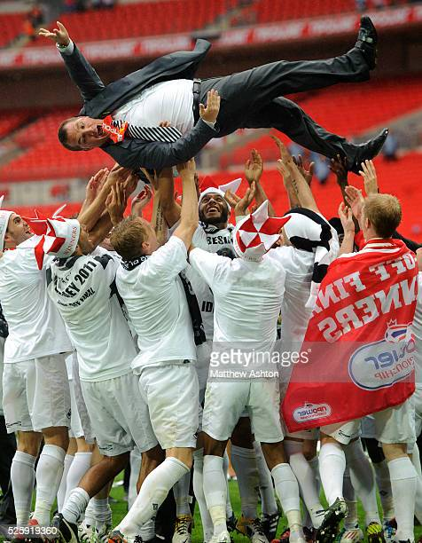 Swansea City players throw Brendan Rodgers the head coach / manager of Swansea City into the air whilst celebrating promotion to the Premier League