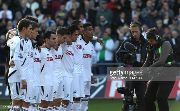 Swansea City Wales players Joe Allen Neil Taylor and Ashley Williams along with their team mates observe a minutes silence after the news that Wales...