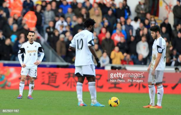 Swansea City's Alejandro Pozuelo Leon Britton and Wilfried Bony stand dejected waiting to restart the match after Tottenham Hotspur's Emmanuel...