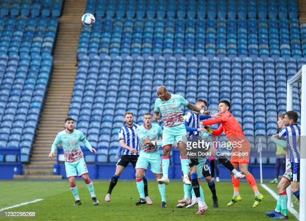 Swansea City's Andre Ayew heads clear under pressure from Sheffield Wednesday's Liam Shaw during the Sky Bet Championship match between Sheffield...
