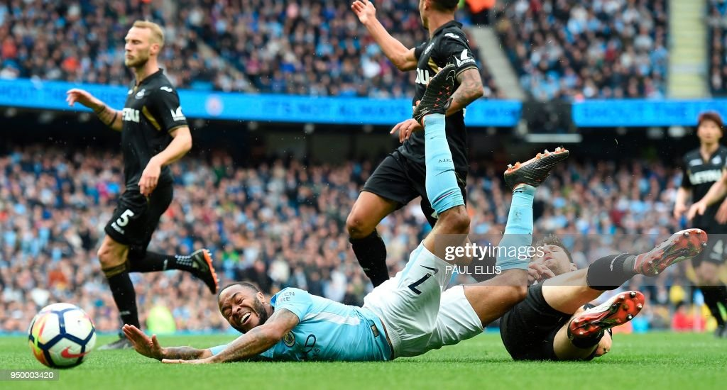 Swansea City's Argentinian defender Federico Fernandez (R) fouls Manchester City's English midfielder Raheem Sterling to concede a penalty during the English Premier League football match between Manchester City and Swansea at the Etihad Stadium in Manchester, north west England, on April 22, 2018. (Photo by Paul ELLIS / AFP) / RESTRICTED TO EDITORIAL USE. No use with unauthorized audio, video, data, fixture lists, club/league logos or 'live' services. Online in-match use limited to 75 images, no video emulation. No use in betting, games or single club/league/player publications. /