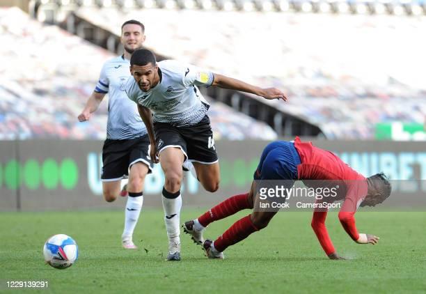 Swansea City's Ben Cabango battles with Huddersfield Town's Juninho Bacuna during the Sky Bet Championship match between Swansea City and...