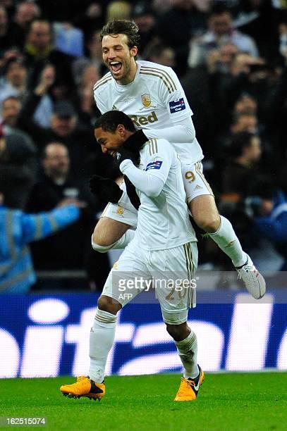 Swansea City's Canadianborn Dutch midfielder Jonathan de Guzman celebrates scoring their fourth goal with Spanish striker Miguel Michu during the...