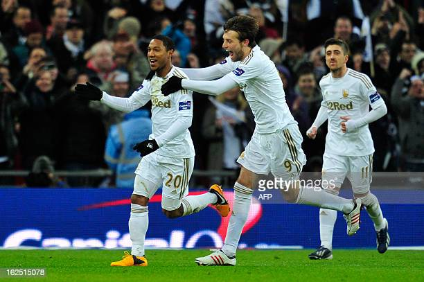 Swansea City's Canadian-born Dutch midfielder Jonathan de Guzman celebrates scoring their fourth goal with Spanish striker Miguel Michu during the...