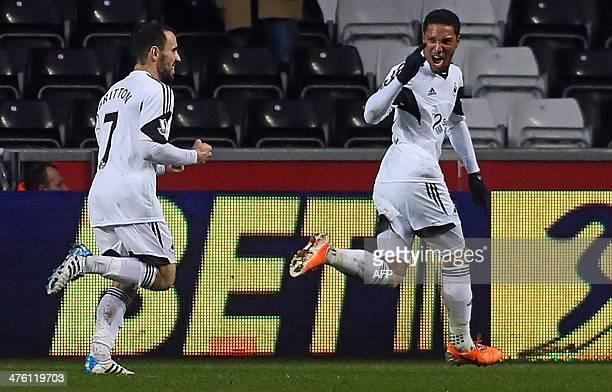 Swansea City's Canadianborn Dutch midfielder Jonathan de Guzman celebrates with Swansea City's English midfielder Leon Britton after scoring the...
