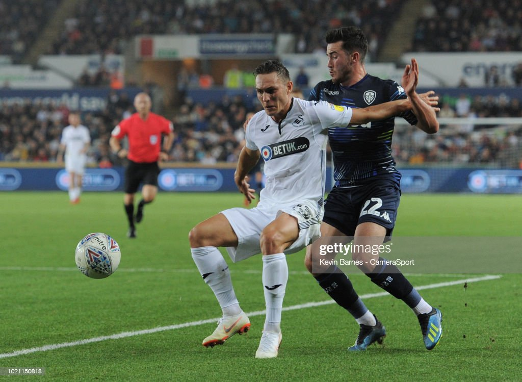 Swansea City's Connor Roberts under pressure from Leeds United's Jack Harrison during the Sky Bet Championship match between City and Leeds United at Liberty Stadium on August 21, 2018 in Swansea, Wales.