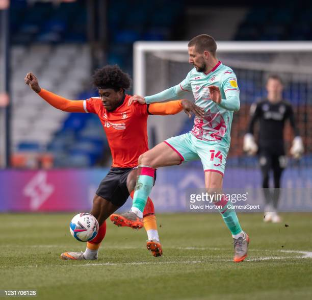 Swansea City's Conor Hourihane battles for possession with Luton Town's Pelly-Ruddock Mpanzu during the Sky Bet Championship match between Luton Town...