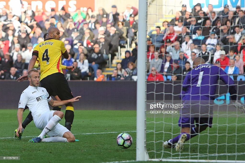 Swansea City's Dutch defender Mike van der Hoorn (L) misses with this attempt on goal during the English Premier League football match between Swansea City and Watford at The Liberty Stadium in Swansea, south Wales on October 22, 2016. / AFP / Geoff CADDICK / RESTRICTED TO EDITORIAL USE. No use with unauthorized audio, video, data, fixture lists, club/league logos or 'live' services. Online in-match use limited to 75 images, no video emulation. No use in betting, games or single club/league/player publications. /
