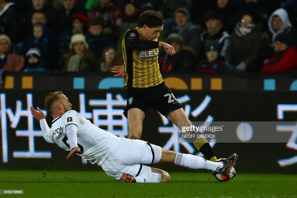 Swansea City's Dutch defender Mike van der Hoorn (L) tackles Sheffield Wednesday's English striker Adam Reach during the English FA Cup 5th round replay football match between Swansea City and Sheffield Wednesday at The Liberty Stadium in Swansea, south Wales on February 27, 2018. / AFP PHOTO / Geoff CADDICK / RESTRICTED TO EDITORIAL USE. No use with unauthorized audio, video, data, fixture lists, club/league logos or 'live' services. Online in-match use limited to 75 images, no video emulation. No use in betting, games or single club/league/player publications. /
