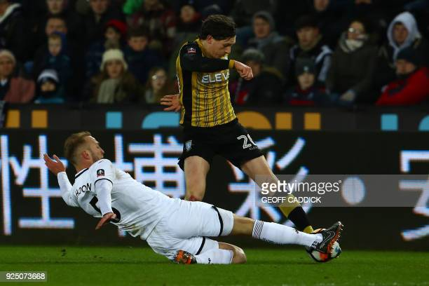 Swansea City's Dutch defender Mike van der Hoorn tackles Sheffield Wednesday's English striker Adam Reach during the English FA Cup 5th round replay...