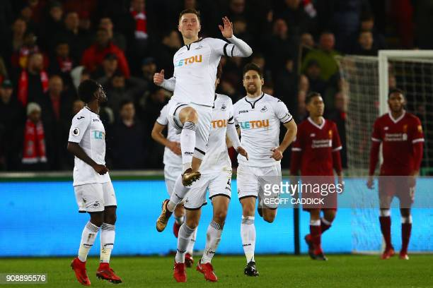 Swansea City's English defender Alfie Mawson celebrates after scoring the opening goal of the English Premier League football match between Swansea...