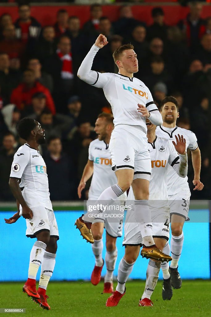 Swansea City's English defender Alfie Mawson (C) celebrates after scoring the opening goal of the English Premier League football match between Swansea City and Liverpool at The Liberty Stadium in Swansea, south Wales on January 22, 2018. / AFP PHOTO / Geoff CADDICK / RESTRICTED TO EDITORIAL USE. No use with unauthorized audio, video, data, fixture lists, club/league logos or 'live' services. Online in-match use limited to 75 images, no video emulation. No use in betting, games or single club/league/player publications. /