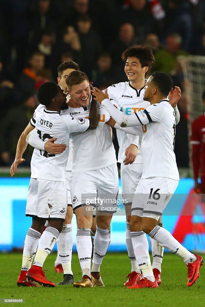 Swansea City's English defender Alfie Mawson (C) celebrates with teammates after scoring the opening goal of the English Premier League football match between Swansea City and Liverpool at The Liberty Stadium in Swansea, south Wales on January 22, 2018. / AFP PHOTO / Geoff CADDICK / RESTRICTED TO EDITORIAL USE. No use with unauthorized audio, video, data, fixture lists, club/league logos or 'live' services. Online in-match use limited to 75 images, no video emulation. No use in betting, games or single club/league/player publications. /