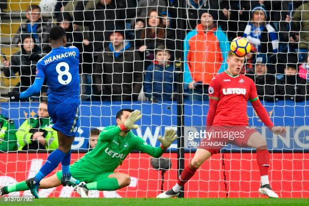 Swansea City's English defender Alfie Mawson heads the ball off the line to save a shot from Leicester City's Nigerian striker Kelechi Iheanacho...