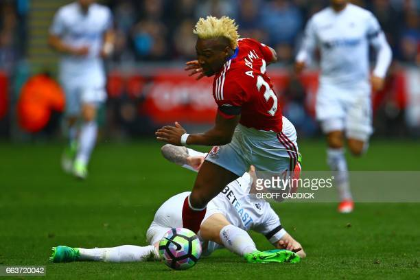 Swansea City's English defender Alfie Mawson is booked for this challenge on Middlesbrough's Spanish midfielder Adama Traore during the English...