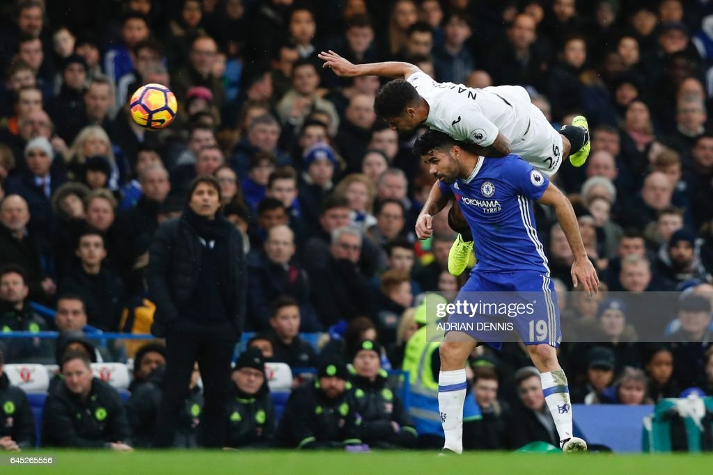 TOPSHOT - Swansea City's English defender Kyle Naughton (top) climbs above Chelsea's Brazilian-born Spanish striker Diego Costa (bottom) during the English Premier League football match between Chelsea and Swansea at Stamford Bridge in London on February 25, 2017. / AFP / Adrian DENNIS / RESTRICTED TO EDITORIAL USE. No use with unauthorized audio, video, data, fixture lists, club/league logos or 'live' services. Online in-match use limited to 75 images, no video emulation. No use in betting, games or single club/league/player publications. /