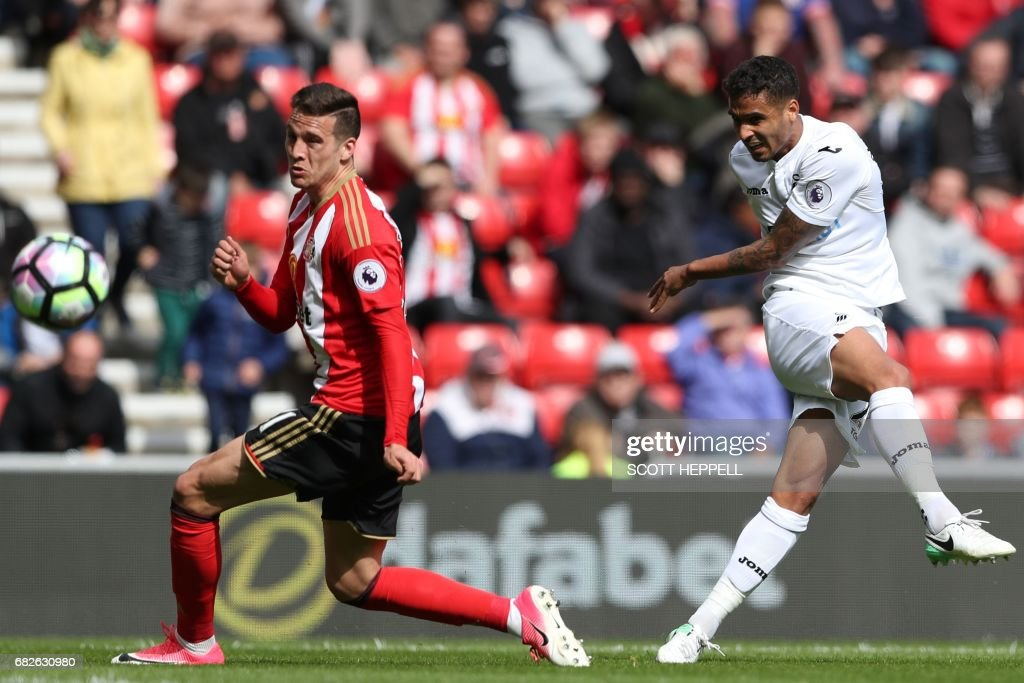 Swansea City's English defender Kyle Naughton (R) shoots past Sunderland's Spanish defender Javier Manquillo to score their second goal during the English Premier League football match between Sunderland and Swansea City at the Stadium of Light in Sunderland, north-east England on May 13, 2017. / AFP PHOTO / Scott Heppell / RESTRICTED TO EDITORIAL USE. No use with unauthorized audio, video, data, fixture lists, club/league logos or 'live' services. Online in-match use limited to 75 images, no video emulation. No use in betting, games or single club/league/player publications. /