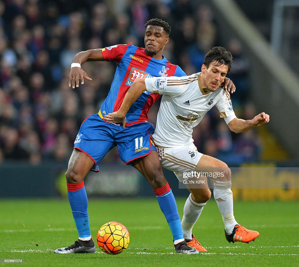 Swansea City's English midfielder Jack Cork (R) tussles with Crystal Palace's Ivorian-born English striker Wilfried Zaha (L) during the English Premier League football match between Crystal Palace and Swansea City at Selhurst Park in south London on December 28, 2015. AFP PHOTO / GLYN KIRK USE. No use with unauthorized audio, video, data, fixture lists, club/league logos or 'live' services. Online in-match use limited to 75 images, no video emulation. No use in betting, games or single club/league/player publications. / AFP / GLYN