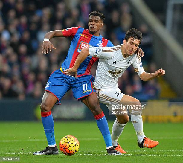 Swansea City's English midfielder Jack Cork tussles with Crystal Palace's Ivorianborn English striker Wilfried Zaha during the English Premier League...