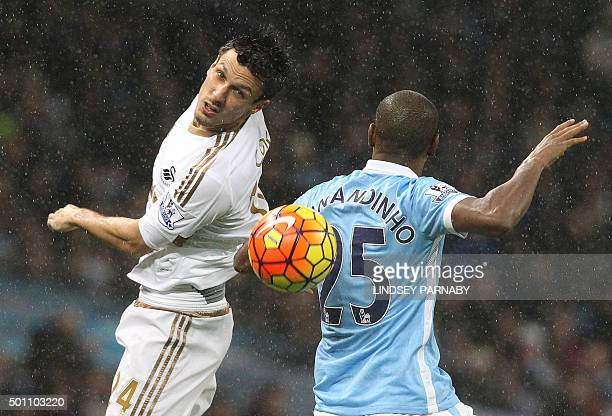 Swansea City's English midfielder Jack Cork vies with Manchester City's Brazilian midfielder Fernandinho during the English Premier League football...