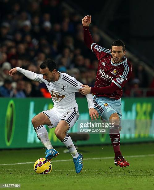 Swansea City's English midfielder Leon Britton and West Ham United's French midfielder Morgan Amalfitalo during the English Premier League football...