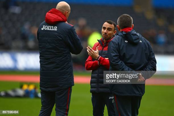 Swansea City's English midfielder Leon Britton interim manager speaks to his assistants on the pitch ahead of the English Premier League football...