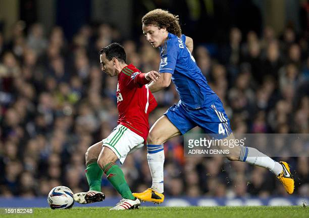 Swansea City's English midfielder Leon Britton is challenged by Chelsea's Brazilian defender David Luiz during the English League Cup first leg...