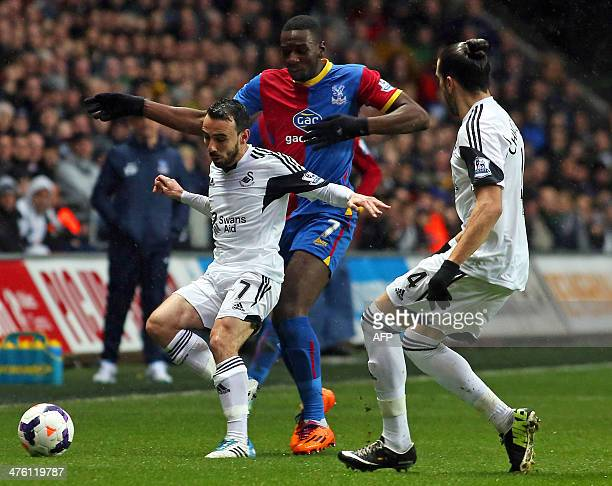 Swansea City's English midfielder Leon Britton vies with Crystal Palace's Frenchborn Congolese midfielder Yannick Bolasie during the English Premier...