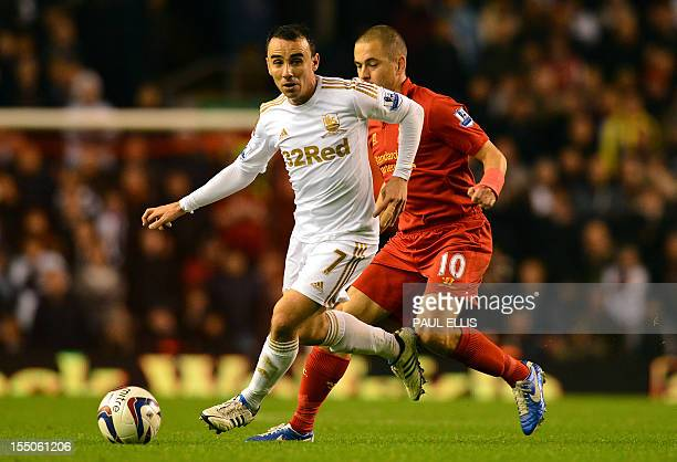 Swansea City's English midfielder Leon Britton vies with Liverpool's English midfielder Joe Cole during the English League Cup Fourth Round football...
