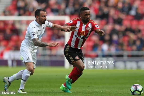 Swansea City's English midfielder Leon Britton vies with Sunderland's English striker Jermain Defoe during the English Premier League football match...