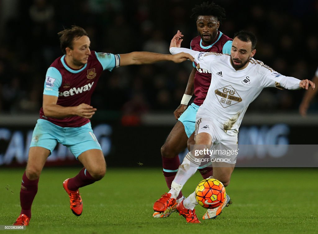 Swansea City's English midfielder Leon Britton (R) vies with West Ham United's English midfielder Mark Noble (L) and West Ham United's Cameroonian midfielder Alex Song during the English Premier League football match between Swansea City and West Ham United at The Liberty Stadium in Swansea, south Wales on December 20, 2015. OR 'LIVE' SERVICES. ONLINE IN-MATCH USE LIMITED TO 75 IMAGES, NO VIDEO EMULATION. NO USE IN BETTING, GAMES OR SINGLE CLUB/LEAGUE/PLAYER PUBLICATIONS. / AFP / Geoff CADDICK