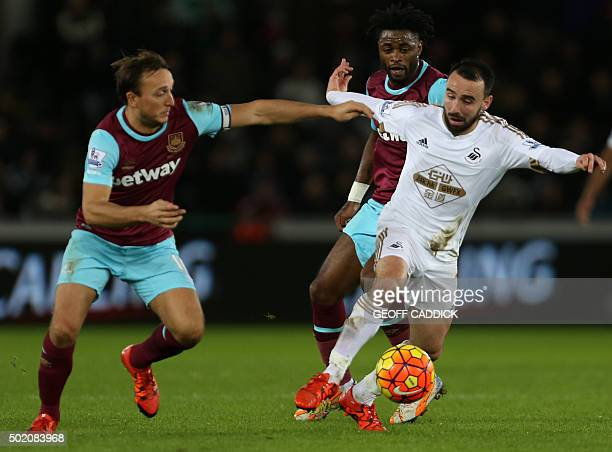 Swansea City's English midfielder Leon Britton vies with West Ham United's English midfielder Mark Noble and West Ham United's Cameroonian midfielder...