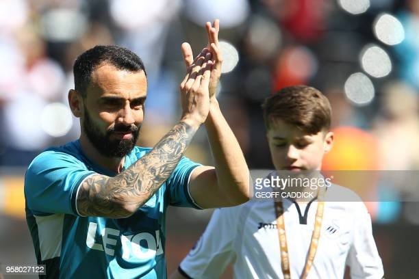 Swansea City's English midfielder Leon Britton waves as he plays his final match for Swansea before the English Premier League football match between...
