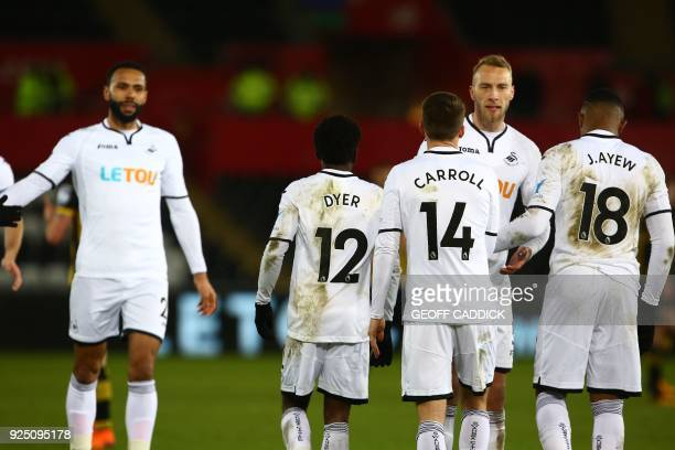 Swansea City's English midfielder Nathan Dyer celebrates with teammates scoring the team's second goal during the English FA Cup 5th round replay...