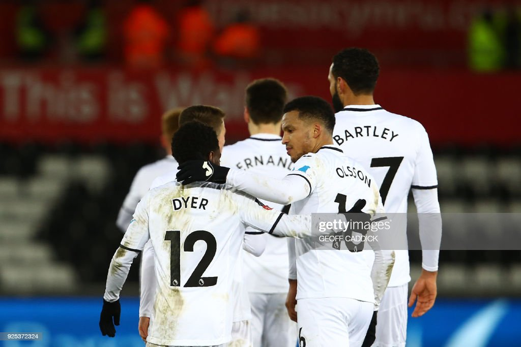 Swansea City's English midfielder Nathan Dyer (L) celebrates with Swansea City's Swedish defender Martin Olsson scoring the team's second goal during the English FA Cup 5th round replay football match between Swansea City and Sheffield Wednesday at The Liberty Stadium in Swansea, south Wales on February 27, 2018. / AFP PHOTO / Geoff CADDICK / RESTRICTED TO EDITORIAL USE. No use with unauthorized audio, video, data, fixture lists, club/league logos or 'live' services. Online in-match use limited to 75 images, no video emulation. No use in betting, games or single club/league/player publications. /