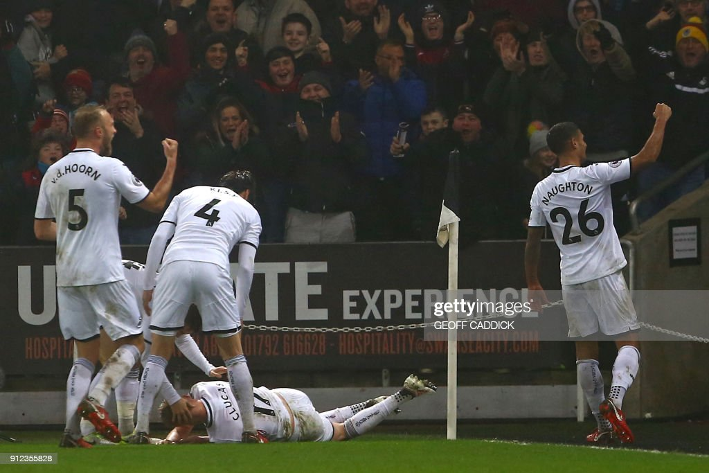 Swansea City's English midfielder Sam Clucas falls to the floor as he celebrates with teammates after scoring his second goal during the English Premier League football match between Swansea City and Arsenal at The Liberty Stadium in Swansea, south Wales on January 30, 2018. / AFP PHOTO / Geoff CADDICK / RESTRICTED TO EDITORIAL USE. No use with unauthorized audio, video, data, fixture lists, club/league logos or 'live' services. Online in-match use limited to 75 images, no video emulation. No use in betting, games or single club/league/player publications. /