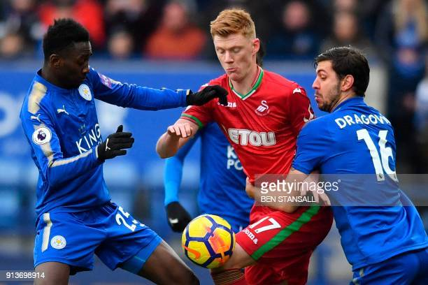Swansea City's English midfielder Sam Clucas is blocked off by Leicester City's Nigerian midfielder Wilfred Ndidi and Leicester City's Austrian...