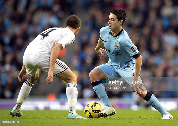 Swansea City's English midfielder Tom Carroll vies for the ball with Manchester City's French midfielder Samir Nasri during the English Premier...