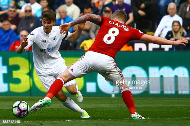 Swansea City's English midfielder Tom Carroll vies with Middlesbrough's English midfielder Adam Clayton during the English Premier League football...