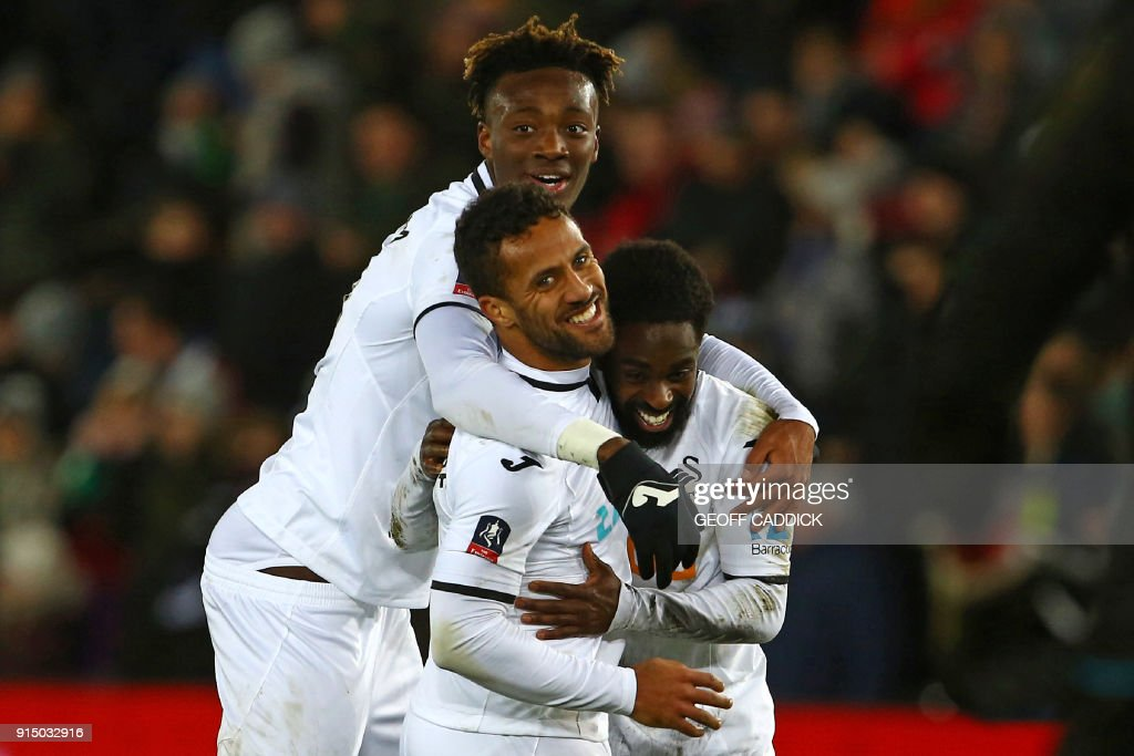 Swansea City's English midfielder Wayne Routledge (C) celebrates with Swansea City's English striker Tammy Abraham (L) and Swansea City's English midfielder Nathan Dyer (R) after scoring their sixth goal during the English FA Cup fourth round replay football match between Swansea City and Notts County at The Liberty Stadium in Swansea, south Wales on February 6, 2018. / AFP PHOTO / Geoff CADDICK / RESTRICTED TO EDITORIAL USE. No use with unauthorized audio, video, data, fixture lists, club/league logos or 'live' services. Online in-match use limited to 75 images, no video emulation. No use in betting, games or single club/league/player publications. /