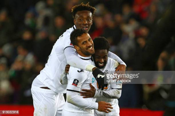 Swansea City's English midfielder Wayne Routledge celebrates with Swansea City's English striker Tammy Abraham and Swansea City's English midfielder...