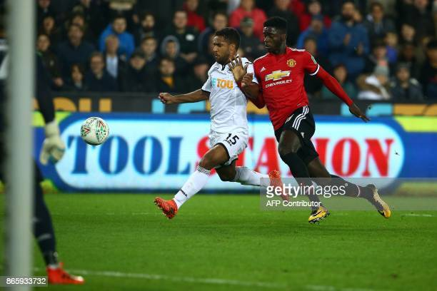 Swansea City's English midfielder Wayne Routledge vies with Manchester United's DR Congoborn defender Axel Tuanzebe during the English League Cup...
