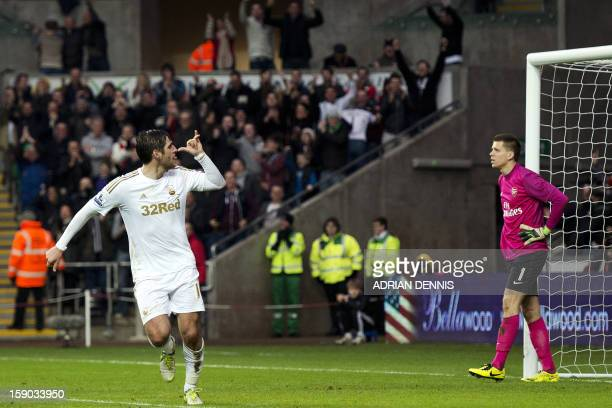 Swansea City's English striker Danny Graham gestures after scoring a late goal to equalise while Arsenal's Polish goalkeeper Wojciech Szczesny looks...
