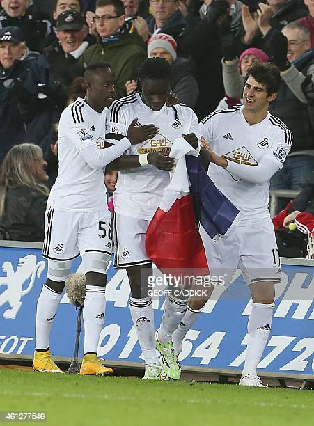 Swansea City's French striker Bafetimbi Gomis holds a French flag as he celebrates after being involved in the equalising goal for Swansea credited...