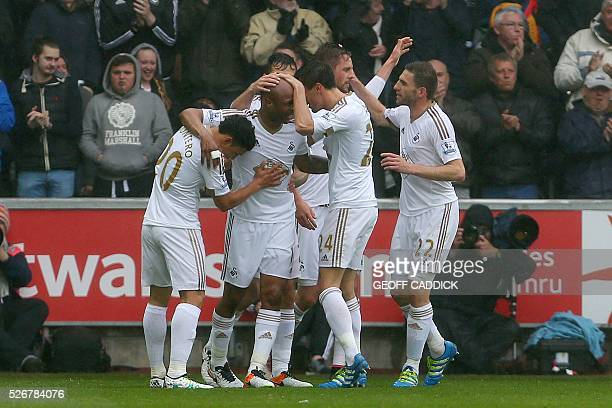 Swansea City's Ghanaian striker Andre Ayew is congratulated after scoring the opening goal during the English Premier League football match between...