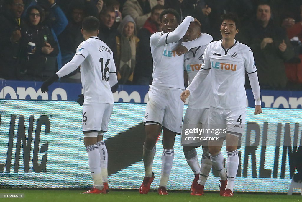 Swansea City's Ghanaian striker Jordan Ayew (2nd R) celebrates with teammates after scoring their second goal during the English Premier League football match between Swansea City and Arsenal at The Liberty Stadium in Swansea, south Wales on January 30, 2018. / AFP PHOTO / Geoff CADDICK / RESTRICTED TO EDITORIAL USE. No use with unauthorized audio, video, data, fixture lists, club/league logos or 'live' services. Online in-match use limited to 75 images, no video emulation. No use in betting, games or single club/league/player publications. /